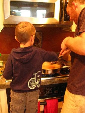 A woman and young boy in the kitchen frosting cookies.