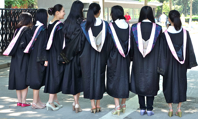Eight girls graduating from college in their gowns, with their backs turned toward the camera