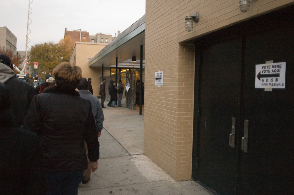 """People are shown standing outside a building in line. Signs on the building read """"vote here"""" in various languages."""