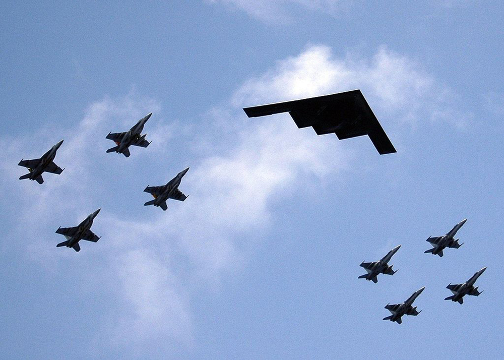 A formation of airplanes featuring fighter jets and a stealth bomber is shown in the sky.