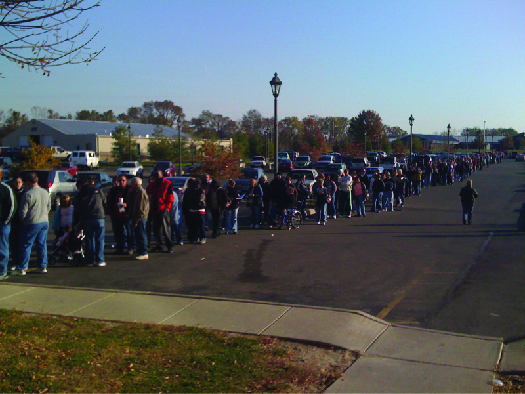 An image of a large group of people lined up along a sidewalk.