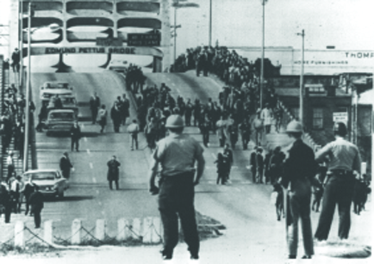 An image of a bridge. On the right of the overpass are several people marching in a large crowd. In the foreground are uniformed people watching the marchers.