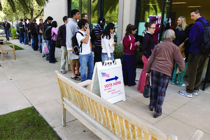 """An image of several people standing in line outside of a building. A sign near the front of the line and the building entrance reads """"Vote Here""""."""
