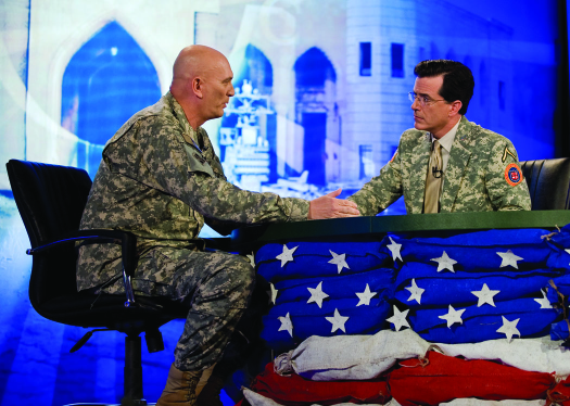An image of Stephen Colbert and Ray Odierno seated on opposite sides of a table, facing each other.