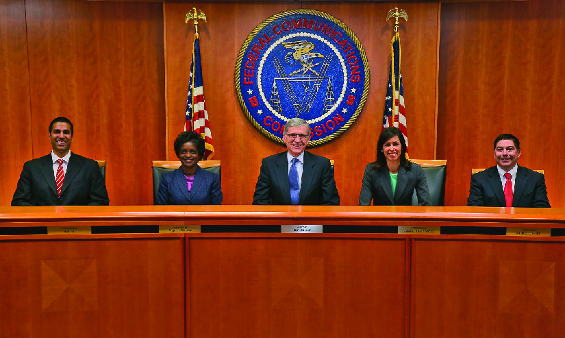 "An image from left to right of Ajit Pai, Mignon Clyburn, Chairman Tom Wheeler, Jessica Rosenworcel and Michael O'Rielly seated in front of a large circular banner reading ""Federal Communications Commission""."