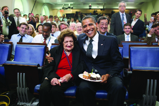 An image of Barack Obama and Helen Thomas seated. Obama holds a plate of cake.
