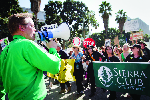 """An image of a person speaking through a bullhorn on the left, and a crowd of people marching down a street on the right. Several marchers are holding a large banner that reads """"Sierra Club""""."""