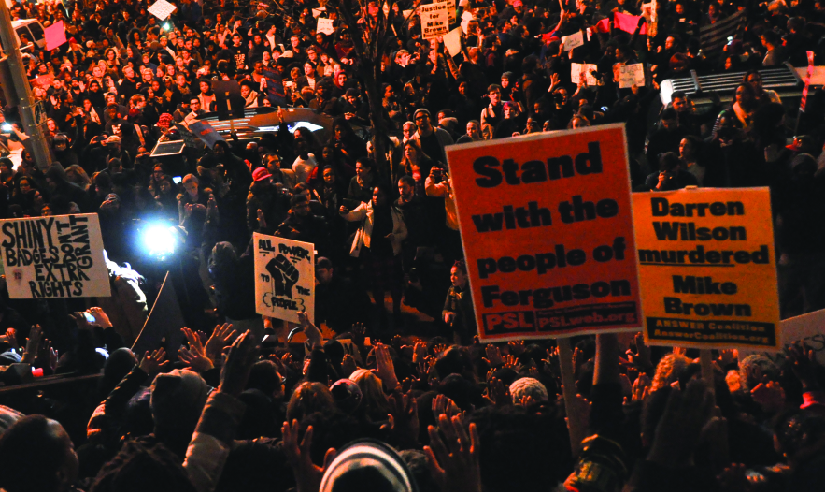 "An image of a large crowd of people, some holding signs that read ""Stand with the people of Ferguson"" and ""Darren Wilson murdered Mike Brown""."