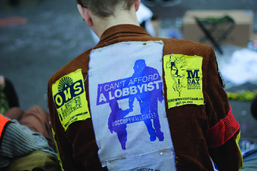 """An image of the back a person wearing a jacket. A patch on the jacket reads """"I can't afford a lobbyist""""."""