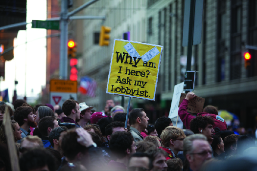 """An image of a crowd of people, one of whom holds a sign that reads """"Why am I here? Ask my lobbyist""""."""