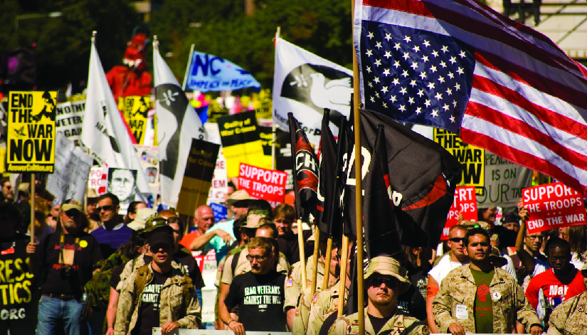 """An image of a group of people, several of whom are holding flags and signs. One of the signs reads """"End the war now"""", and another reads """"Support the troops, end the war""""."""