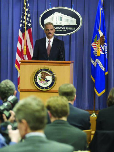 A photo of Eric Holder holding a press conference.