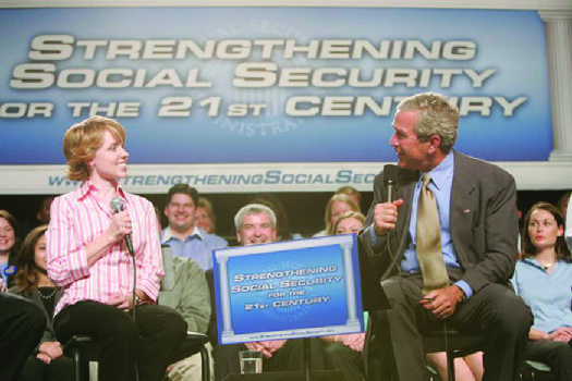 """A photo of George W. Bush speaking at an event. The banner behind him says """"Strengthening Social Security for the 21st Century."""""""