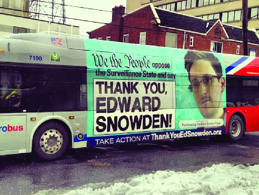 """An ad on the side of a bus featuring a photo of Edward Snowden. The text says """"We the people oppose the Surveillance State and say 'Thank you, Edward Snowden!'"""""""
