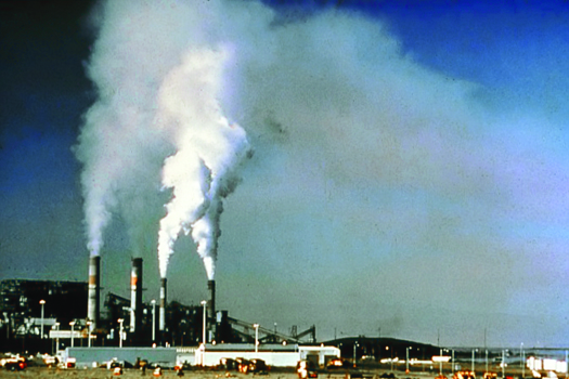 An image of a power plant with large columns of smoke billowing out of its four towers.