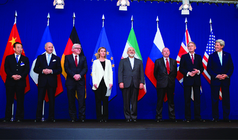 An image of the ministers of foreign affairs and other officials standing on a stage, each in front of the flag of their country.