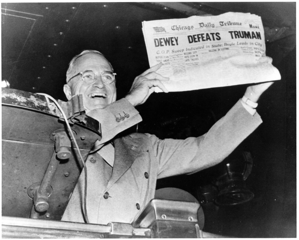 "A smiling Truman holds up a Chicago Tribune newspaper with the headline, ""DEWEY DEFEATS TRUMAN"""