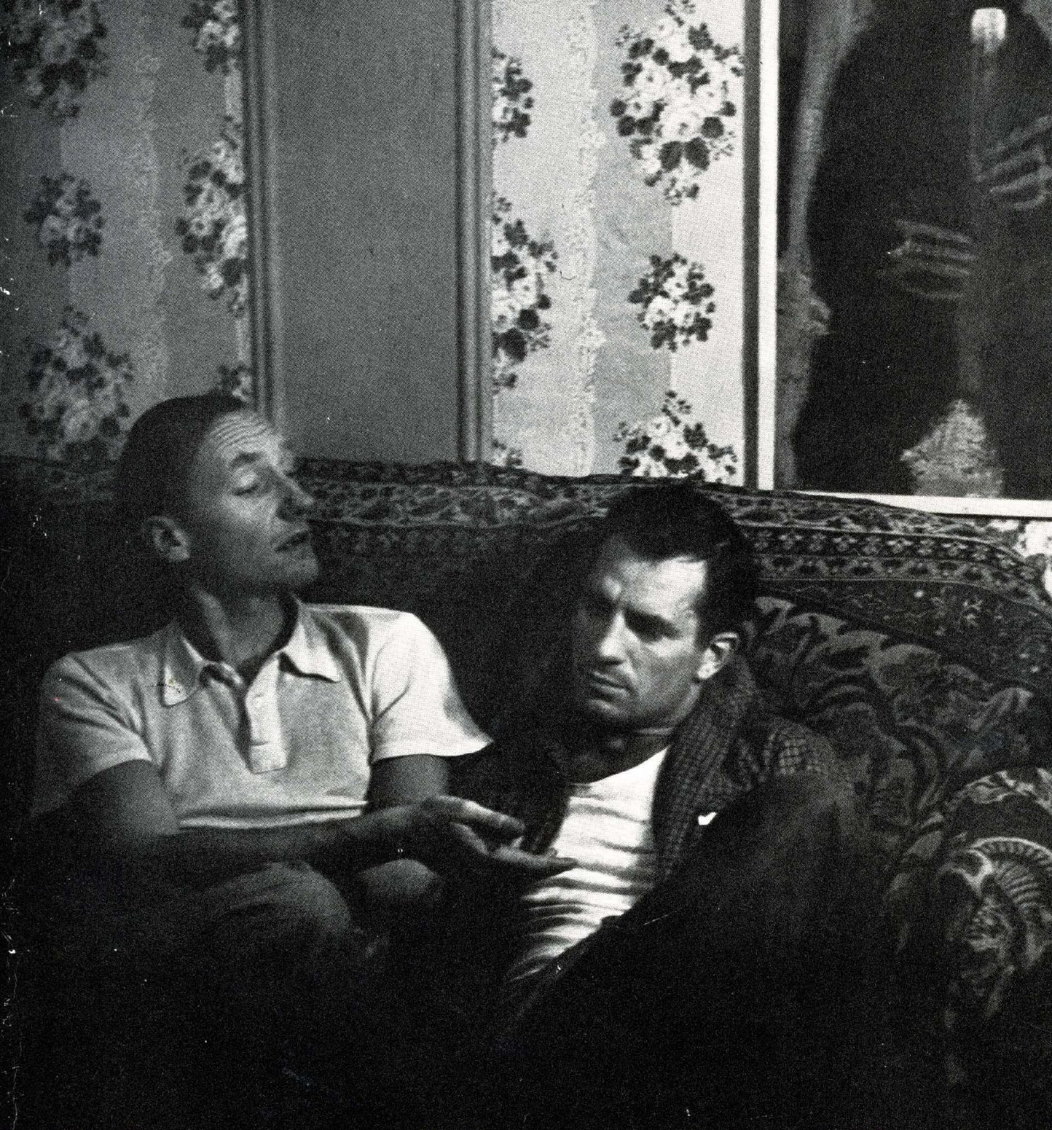 Two men sit on an oriental patterned couch. Ginsberg is on the left, turning towards Kerouac and raising his eyebrows.