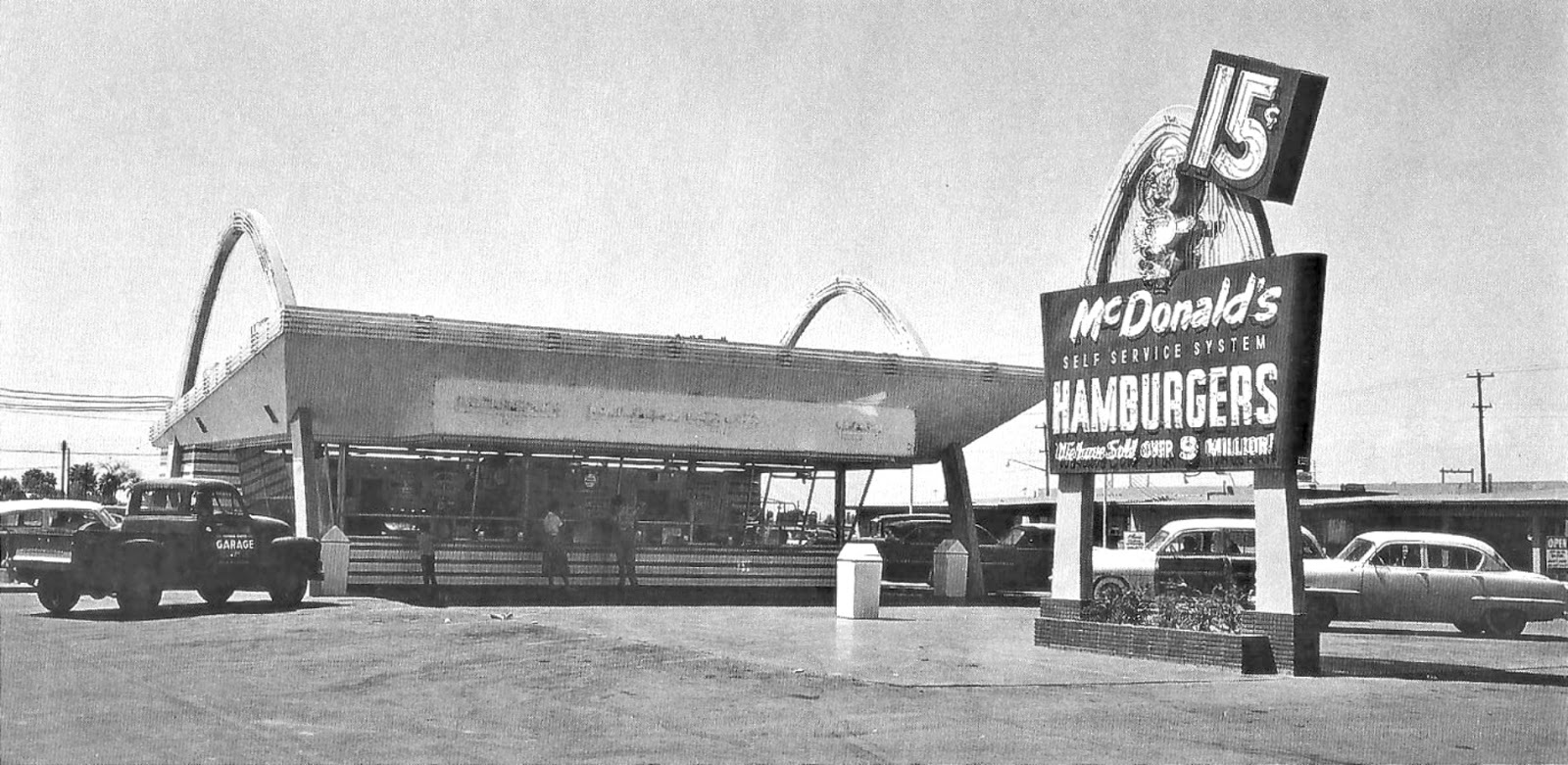 "The McDonald's building is bookended by two giant arches. A large free-standing sing in front of the building read ""15 cents; McDonald's self service system Hamburgers; welcome sold over 9 million."" The sign has only a single arch."