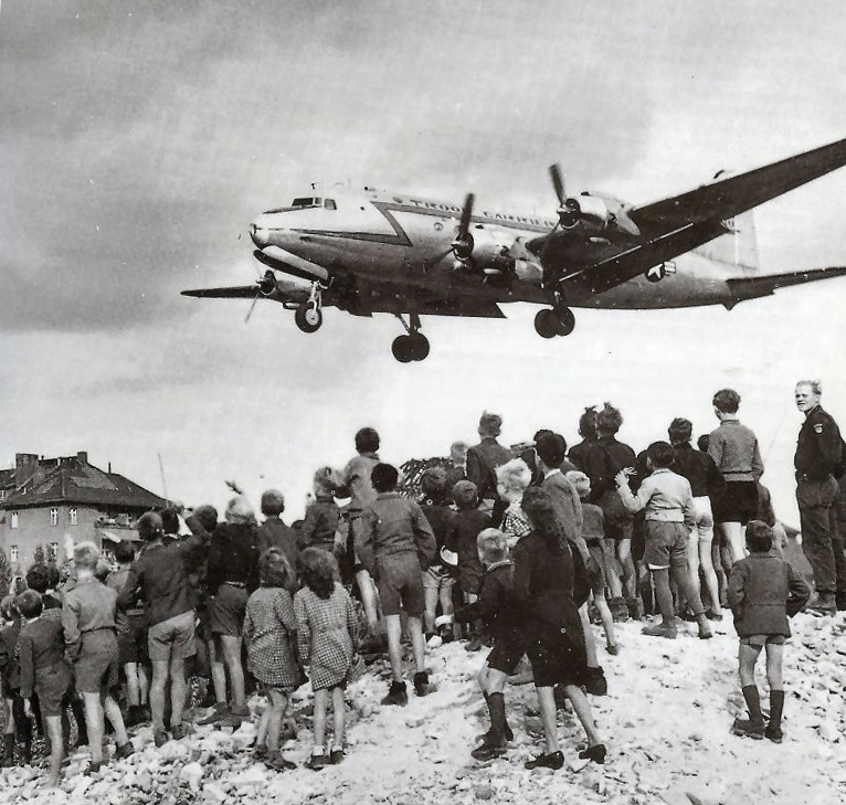 A crowd of people, mostly children, stand on a hill.  Their backs are to the camera as they look up towards an airplane that is coming down for landing close by.