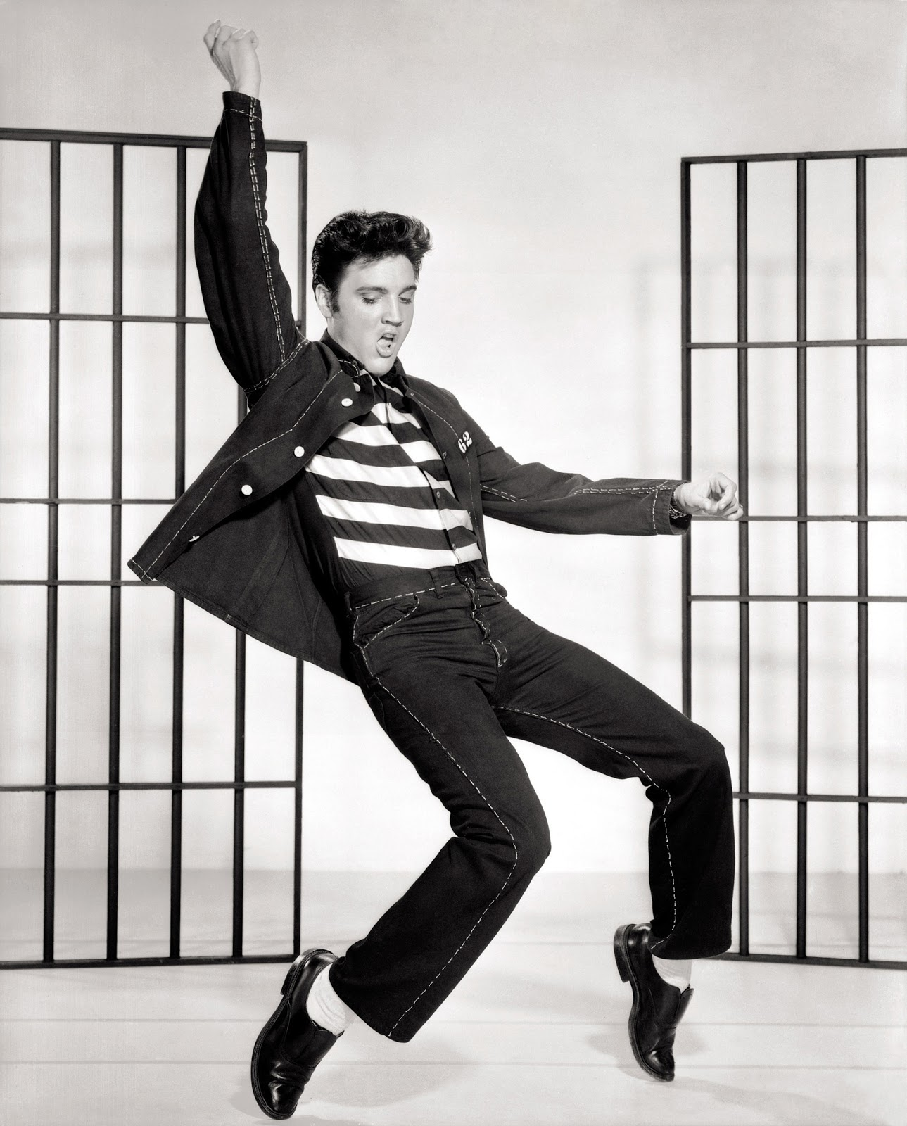 Elvis Presley in a striped T-shirt and matching jeans/jacket set, executes a dance move on tip-toe in front of movie-set jail bars.