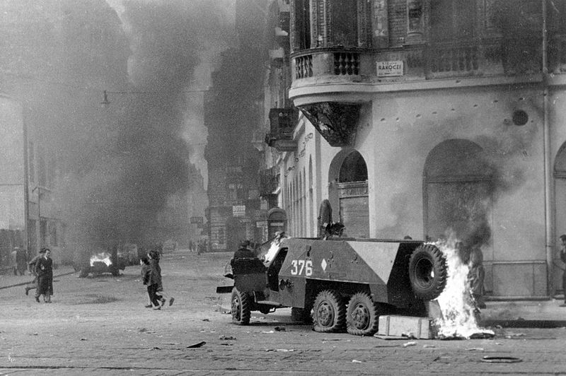 Two military vehicles are burning in a street clouded with dark smoke. Several people are walking in the street.