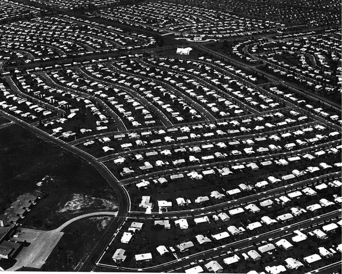 Aerial view of a homogeneous suburban neighborhood shows rows and rows of evenly spaced, identical houses.