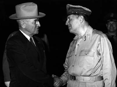 A picture of President Truman in a suit and hat shaking the hand of General Macarthur's.