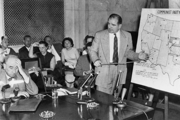"McCarthy stands with a pointer stick in front of a map of the U.S. A partial heading of the map can be seen, reading ""Communist Party."" Several people in the courtroom are holding their heads and looking away from McCarthy, including Joseph Welch, whom McCarthy is facing."