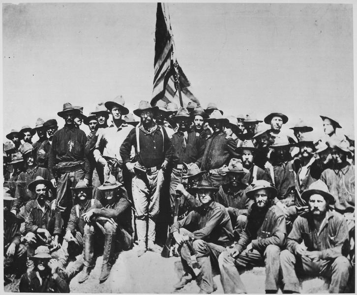 """""""Teddy's colts,"""" at the top of the hill which they captured in the battle of San Juan."""" Colonel Theodore Roosevelt and his Rough Riders, 1898. (U.S. National Archives and Records Administration) [Public domain], via Wikimedia Commons."""