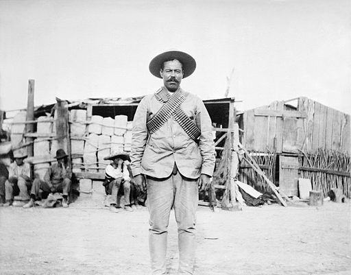 """Francisco """"Pancho"""" Villa wearing bandoliers in front of an insurgent camp. By Bain News Service derivative work: Hic et nunc [Public domain], via Wikimedia Commons"""