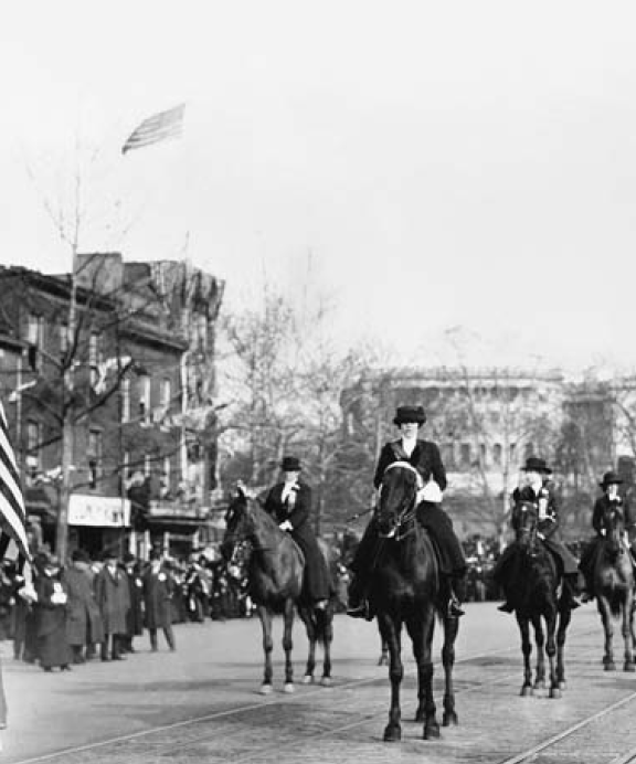 Women suffragists at the head of the parade, marching down Pennsylvania Avenue, with the U.S. Capitol in background, on March 3, 1913.  Author Unknown, [Public Domain] via Library Congress.