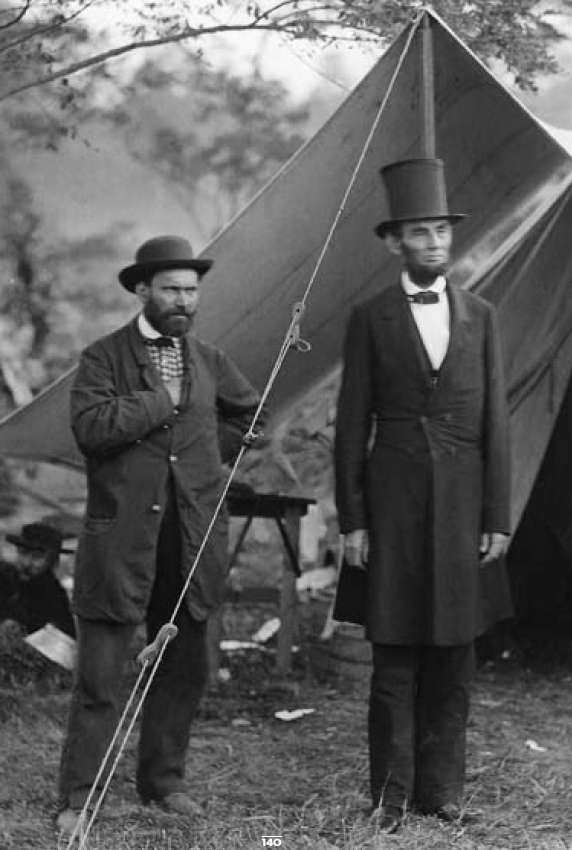 Abraham Lincoln stands outside a tent with a man. [Public Domain]